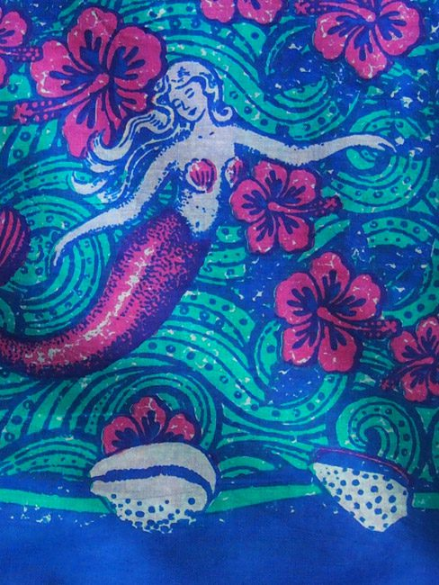 Royal blue and aqua cotton sarong or beach wrap with dreamy mermaid floating in a sea of hibiscus. Close up